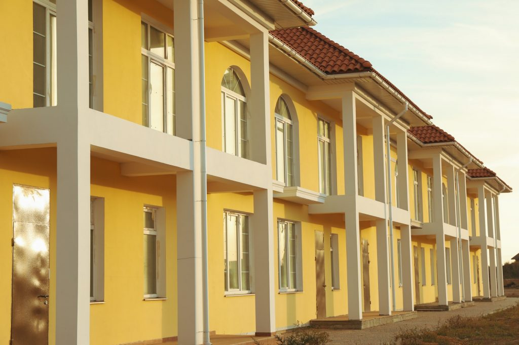 Beautiful new yellow townhouses with red - brown roof